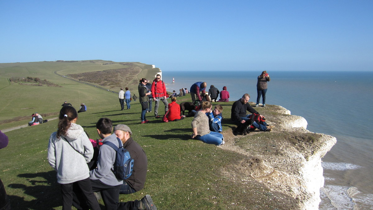 People near the edge of the chalk cliffs at Beachy Head