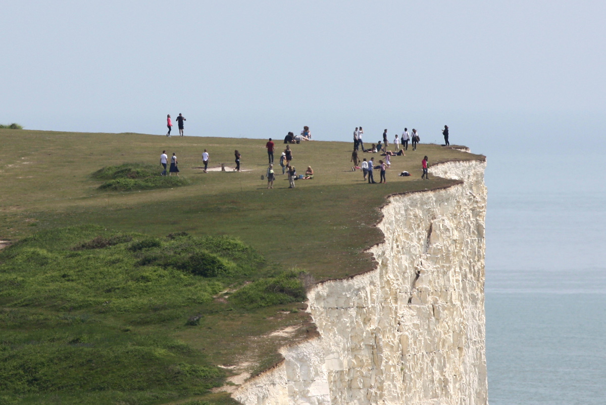 People near the edge of the cliff at Birling Gap